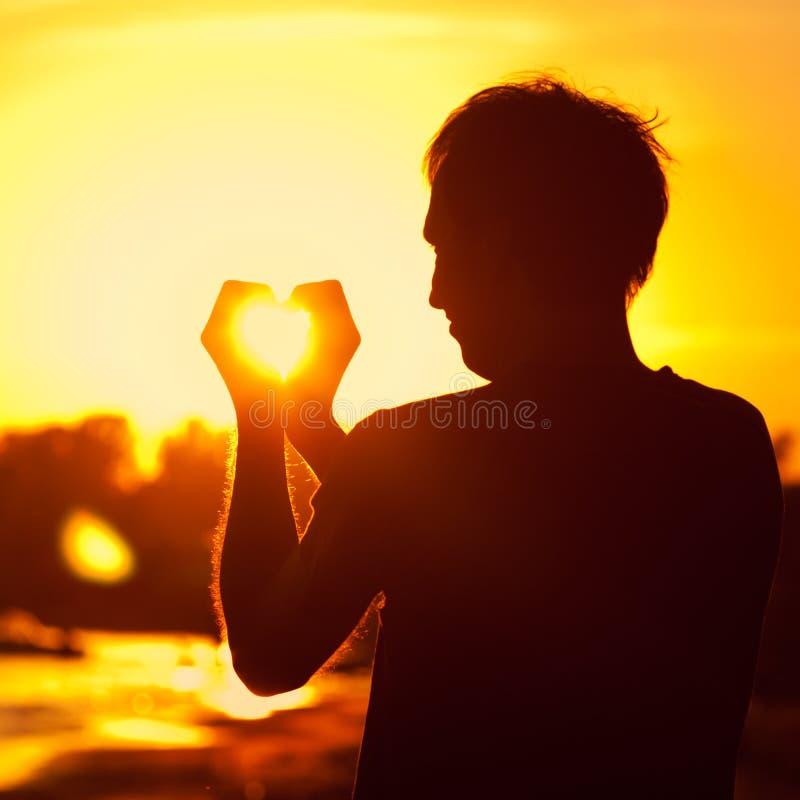 Удерживание человека в руках заходящее солнце стоковое изображение rf
