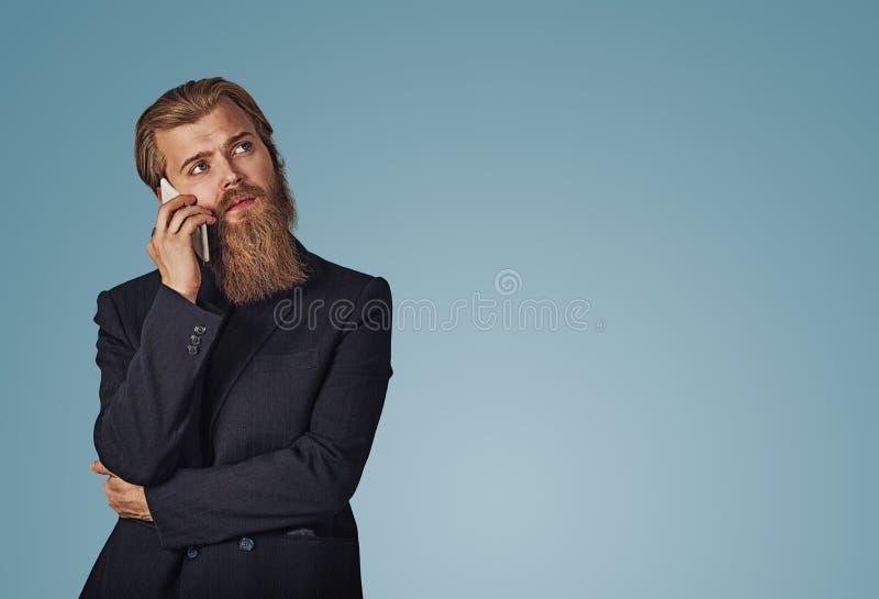Удерживание человека смотря вверх говоря говорить на мысли телефона стоковое изображение