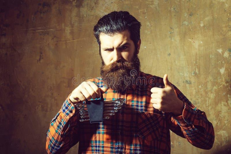 Удерживание человека хмурого взгляда бородатое установило ключей с большими пальцами руки вверх стоковая фотография rf