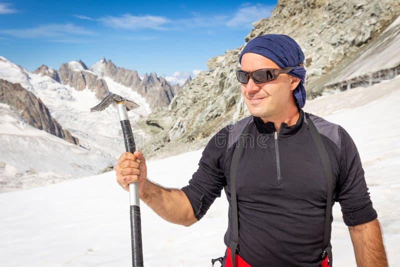 Удерживание alpinist альпиниста представляя инструмент оси льда стоковые фото
