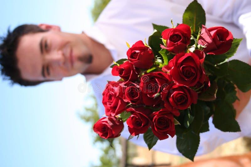 удерживания человека розы вне молодые стоковое изображение