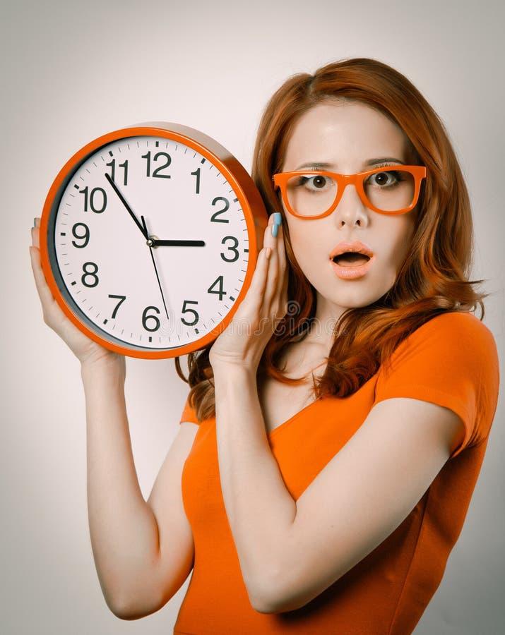 Удивленная девушка redhead с огромным будильником стоковые фото