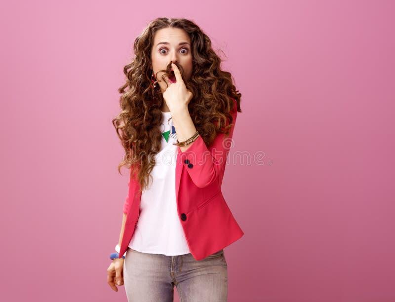 Удивленная женщина на розовой предпосылке делая усик от волос стоковое фото
