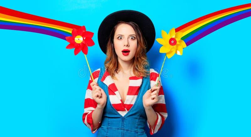 Удивленная женщина с pinwheel и радугой стоковые фото