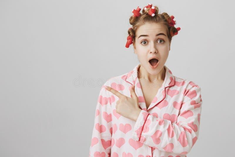 Удивленная и сотрясенная girly девушка в волос-curlers и pyjamas с сердцем печатает показывать налево с forefinger и стоковое фото rf