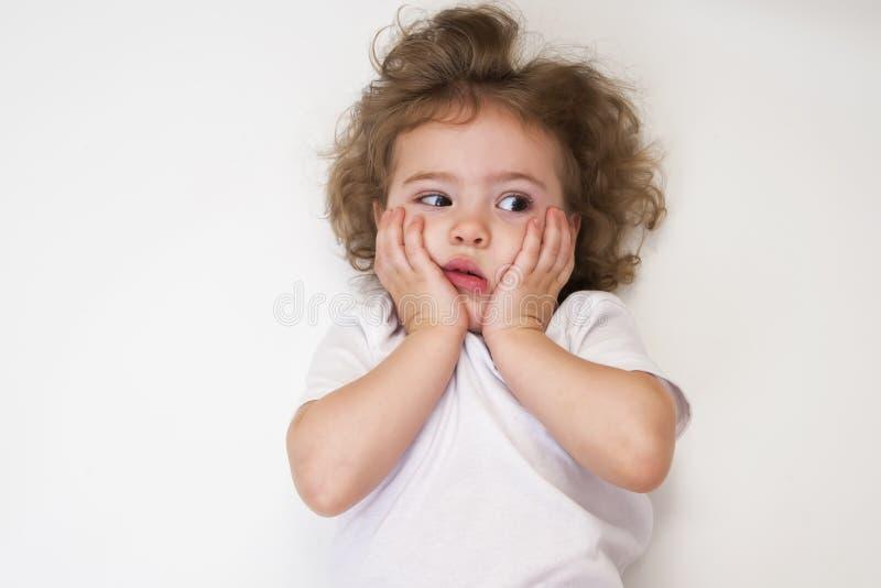 Удивленная маленькая девочка в белой рубашке стоковое фото