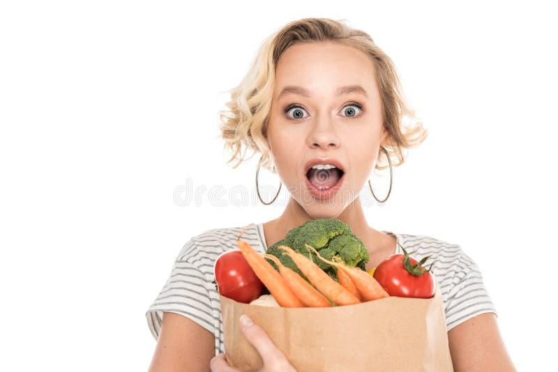 удивленная молодая женщина держа продуктовую сумку и смотря камеру стоковое фото rf