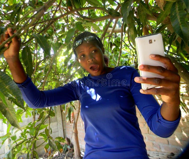 Удивленная молодая женщина смотря в мобильный телефон стоковое изображение