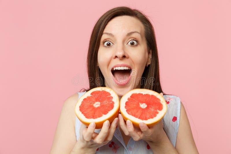 Удивленная смешная молодая женщина держа halfs удерживания 2 рта широкие открытые свежего зрелого грейпфрута изолированного на ро стоковая фотография rf