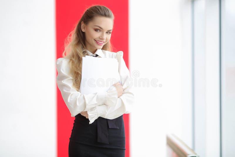 Удивленная стильная девушка в белых одеждах держа папку с документами и смотря камеру стоковое изображение rf