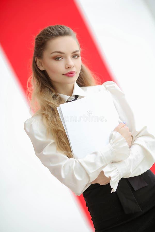 Удивленная стильная девушка в белых одеждах держа папку с документами и смотря камеру стоковая фотография