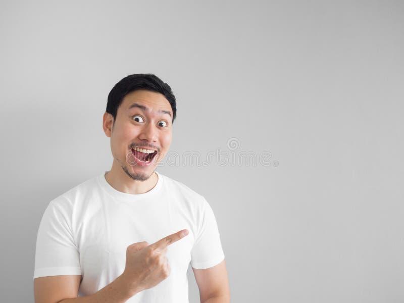 Удивленная сторона счастливого человека в белом свете рубашки - сером backgroun стоковое изображение