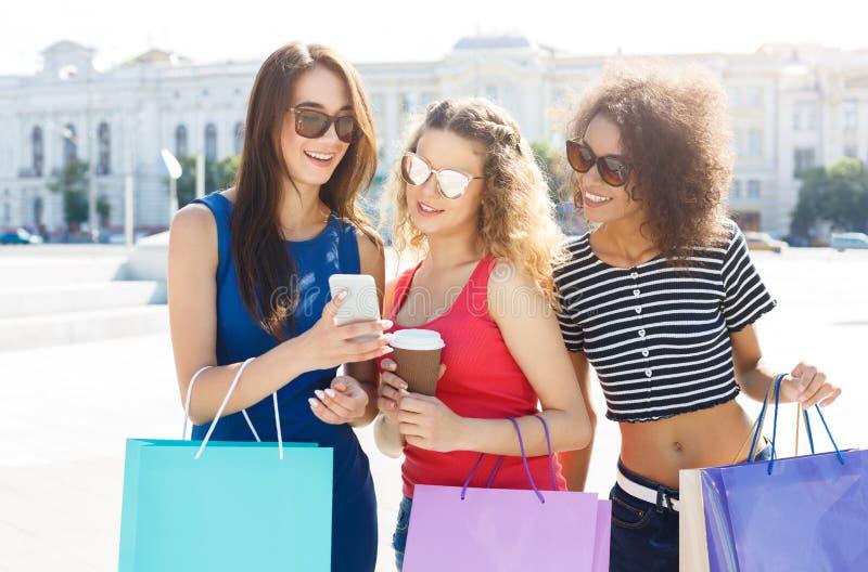 Удивленные женские друзья с smartphone outdoors стоковые изображения rf