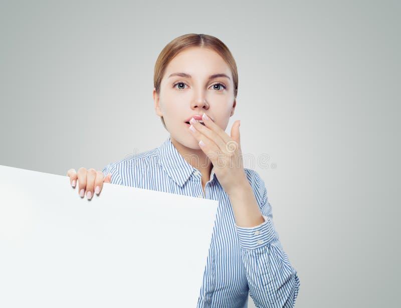 Удивленные коммерсантка или студент молодой женщины показывая белую пустую предпосылку доски с космосом экземпляра для seo стоковые фотографии rf