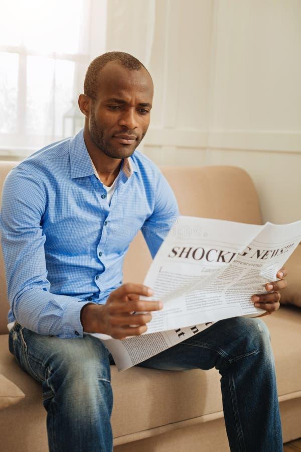 Удивленные новости человека читая самые последние стоковая фотография rf