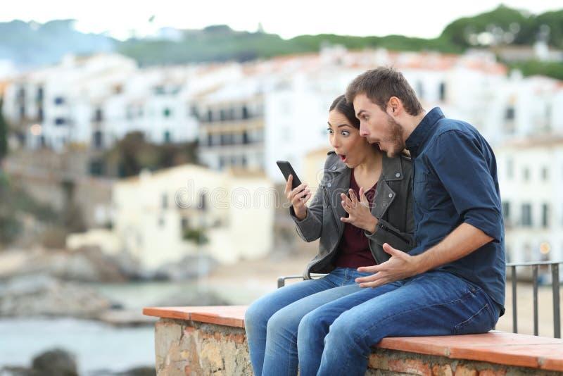Удивленные пары на новостях каникул читая по телефону стоковые фото