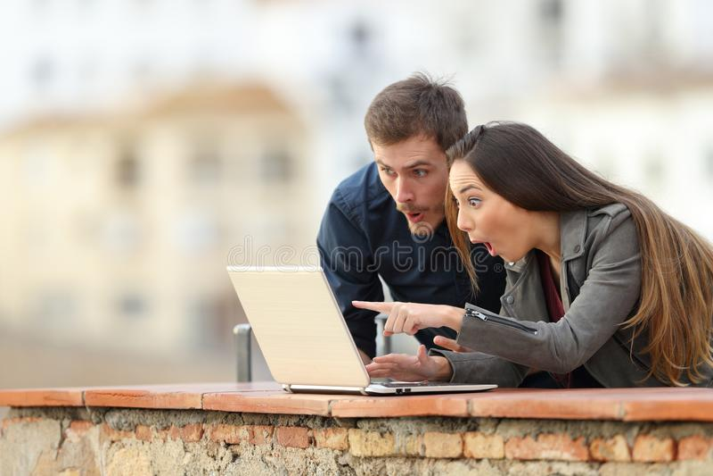 Удивленные пары проверяя содержание ноутбука в балконе стоковая фотография