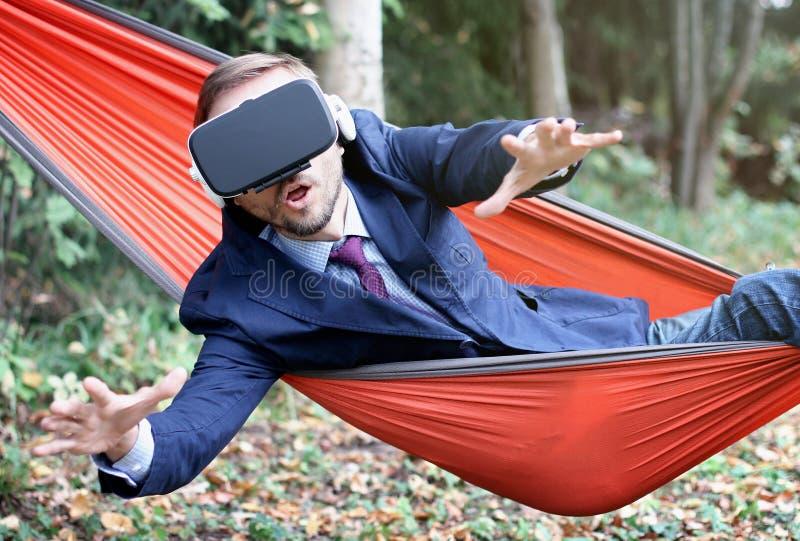 Удивленный бизнесмен использует стекла vr, отдыхая в гамаке Вир стоковые изображения rf