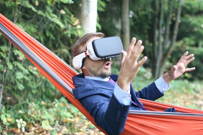 Удивленный бизнесмен использует стекла vr, отдыхая в гамаке на n стоковое изображение rf