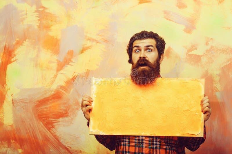 Удивленный бородатый человек держа текстуру краски оранжевого масла на холсте стоковое фото