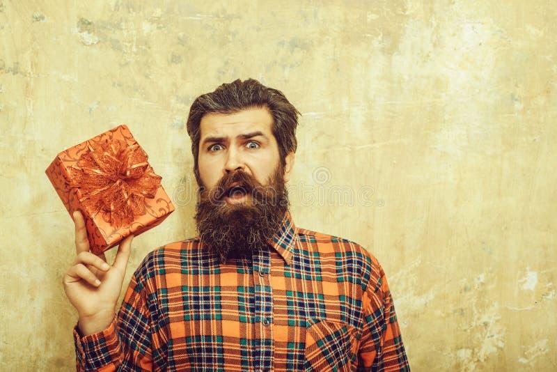 Удивленный бородатый человек с красной подарочной коробкой с смычком стоковое изображение rf