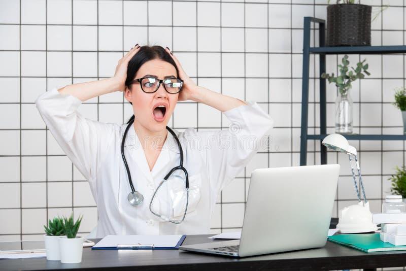 Удивленный женский доктор смотря компьтер-книжку Врач на ее работая офисе Непредвиденные новости или результаты медицинских анали стоковая фотография
