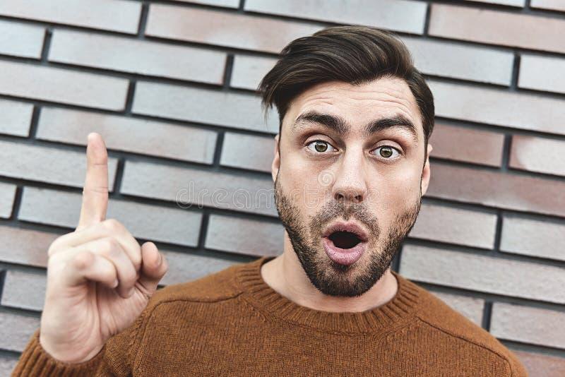 Удивленный кавказский человек с идеей или вопросом указывая палец со счастливой стороной, одно стоковая фотография