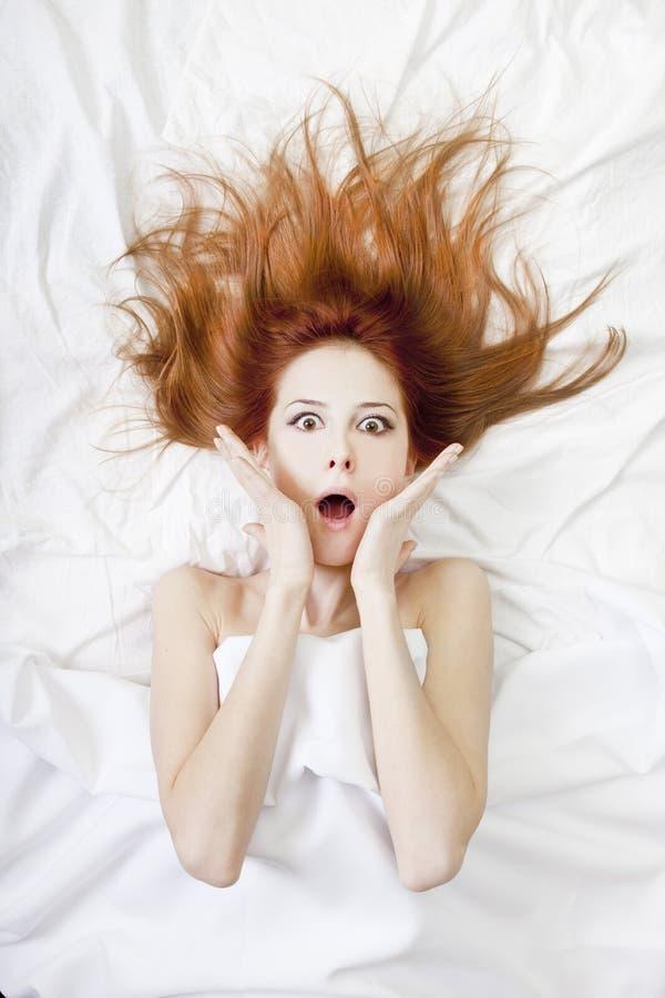 удивленный красный цвет девушки кровати с волосами стоковая фотография