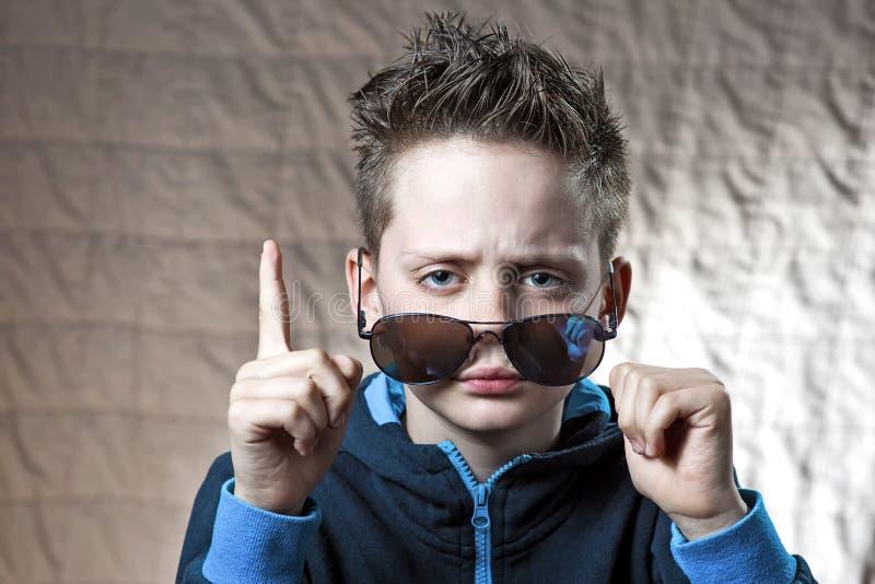 Удивленный мальчик в голубом солнцезащитном креме который получил идею стоковое изображение