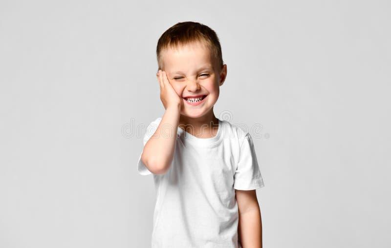 Удивленный мальчик смотря камеру Красивый счастливый ребенок, изолированный на белой предпосылке стоковое фото