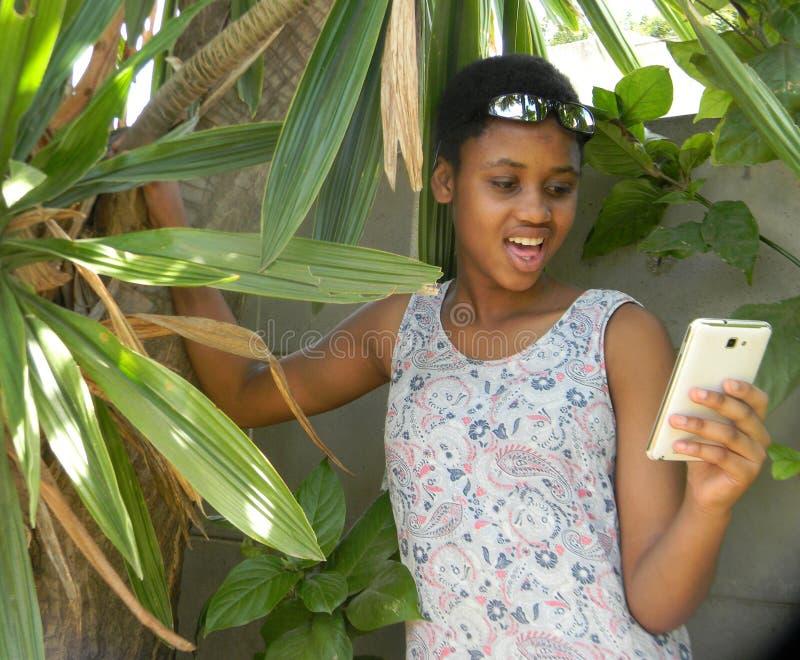 Удивленный мобильный телефон просматривать молодой женщины стоковое фото rf