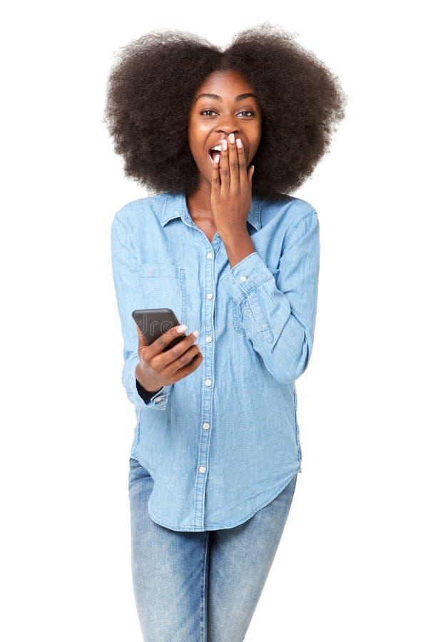 Удивленный мобильный телефон удерживания молодой женщины против изолированной белой предпосылки стоковые изображения