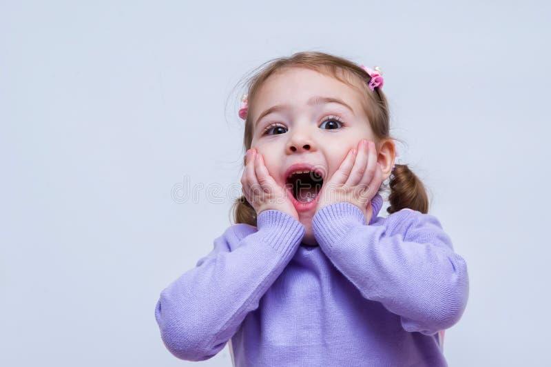 Удивленный ребёнок и положенный ее руке на голову стоковое изображение rf