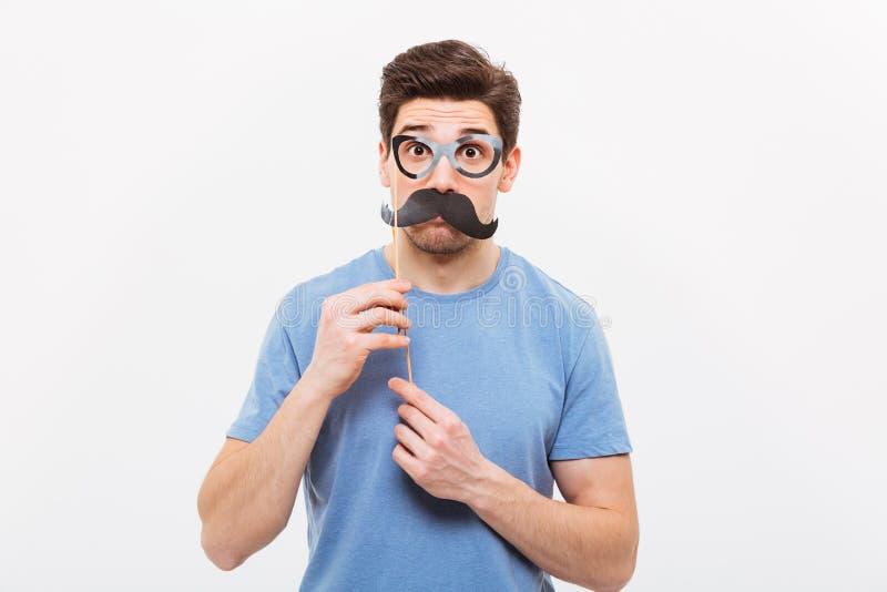 Удивленный человек в поддельном усике и eyeglasses смотря камеру стоковые изображения
