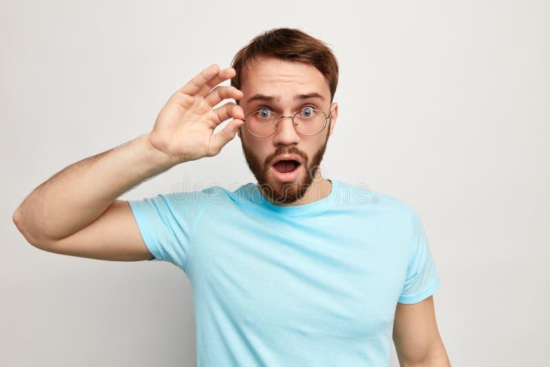 Удивленный человек одел случайно смотреть через стекла стоковое изображение rf