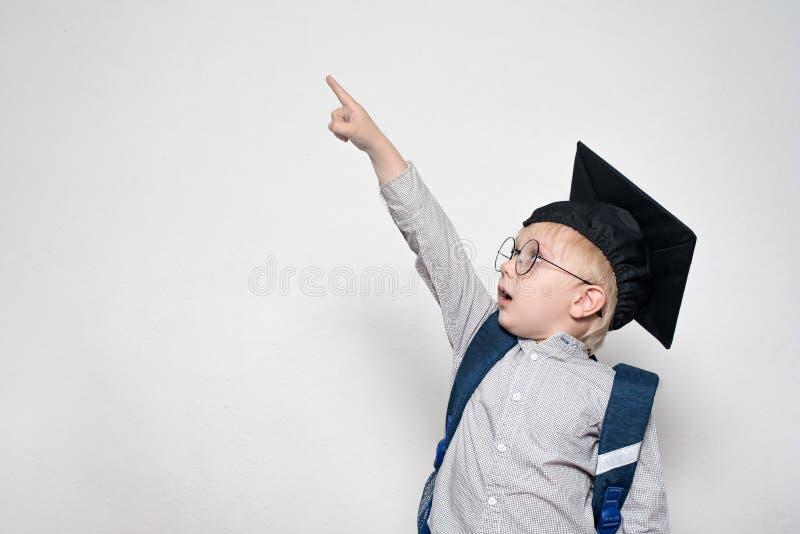 Удивленный школьник в костюме, стеклах и академичной шляпе указывает его палец вверх r o стоковая фотография rf
