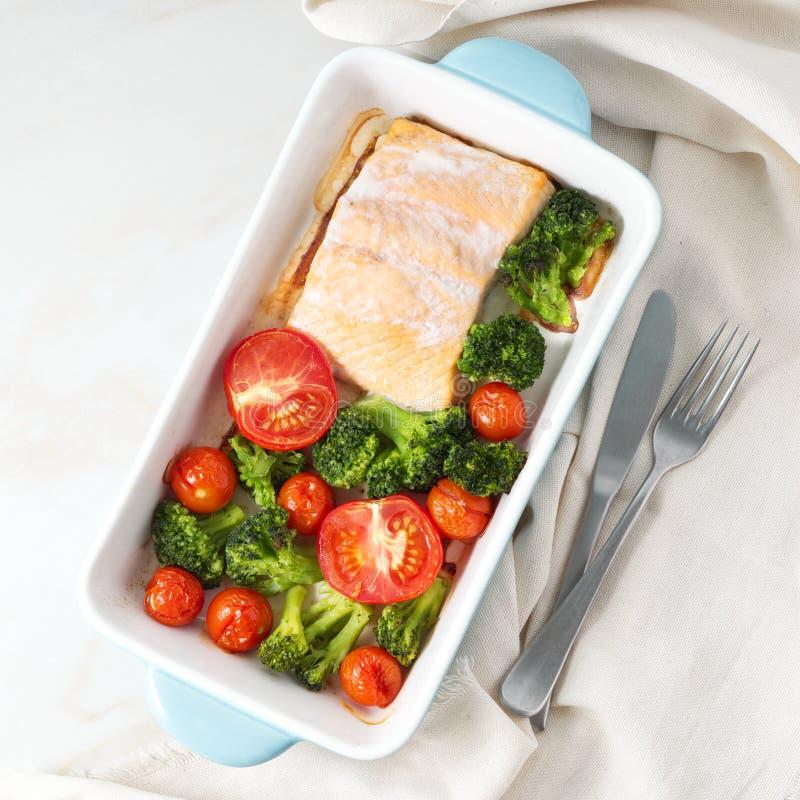Удите семг испеченные в печи с овощами - брокколи, томатах Еда здорового питания, белый мраморный фон, взгляд сверху стоковое фото