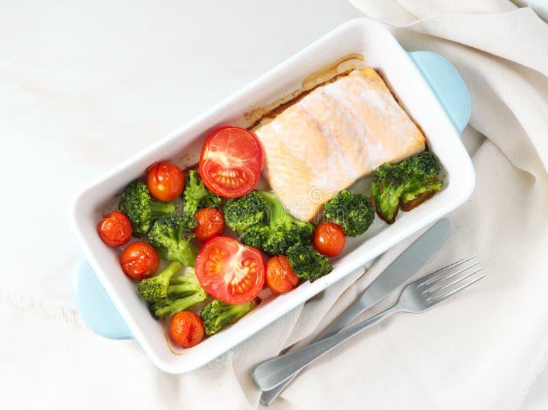 Удите семг испеченные в печи с овощами - брокколи, томатах Еда здорового питания, белый мраморный фон, взгляд сверху стоковое изображение