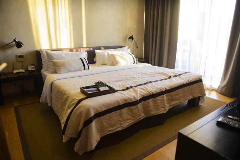 Удобная комната роскошного отеля с подушками и кровать в утре стоковые изображения rf