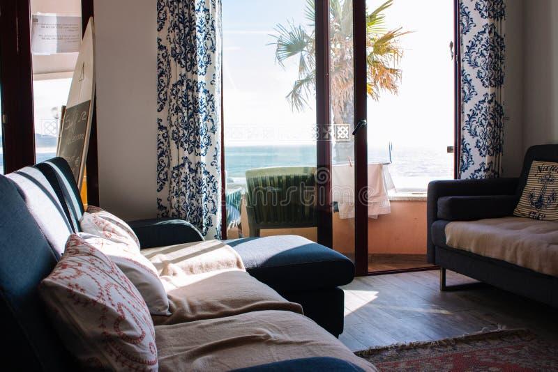 Удобная комната с софой и балкон с видом на море Уютный интерьер квартиры Живущая комната со стильными оформлением и мебелью стоковые фотографии rf