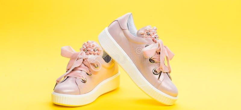 Удобная концепция обуви Милые ботинки на желтой предпосылке Обувь для девушек или женщин украшенных с жемчугом отбортовывает стоковое изображение