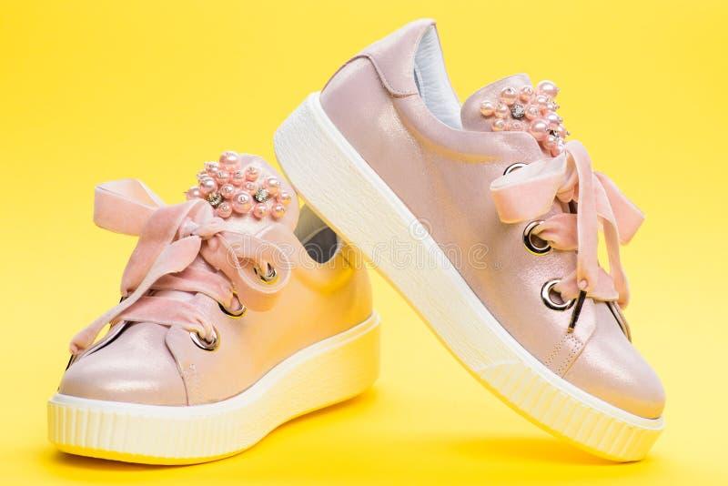 Удобная концепция обуви Обувь для девушек или женщин украшенных с жемчугом отбортовывает Милые ботинки на желтой предпосылке стоковые фото
