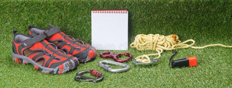 Удобные ботинки для идти в древесины и вещи для обнаружения людей на зеленой предпосылке стоковая фотография rf