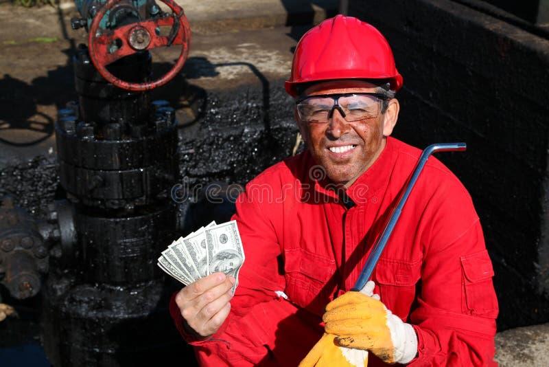Удовлетворенные деньги удерживания работника на нефтянном месторождении стоковые фото
