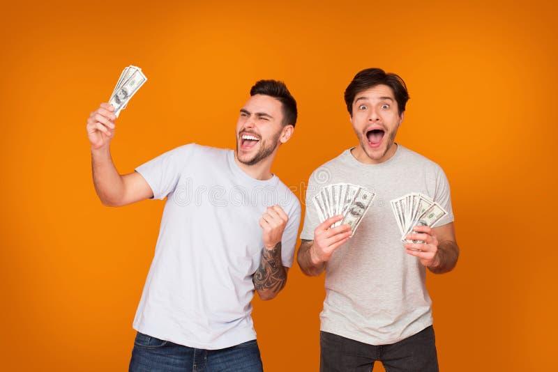 Удовлетворенные люди держа пук банкнот денег стоковые фотографии rf