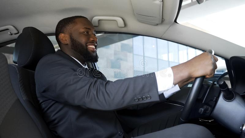 Удовлетворенный человек в деловом костюме сидя в автомобиле, успешном приобретении, счастье стоковая фотография