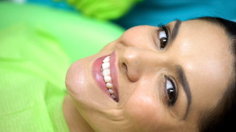 Удовлетворяемая дама после успешного сломленного ремонта зуба, современного астетического зубоврачевания стоковые фотографии rf