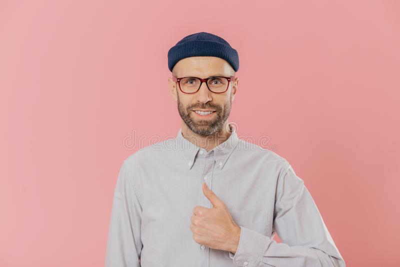 Удовлетворяемый привлекательный человек имеет умоляющий взгляд, поднимает большой палец руки, соглашается с что-то, улыбками счас стоковое фото rf