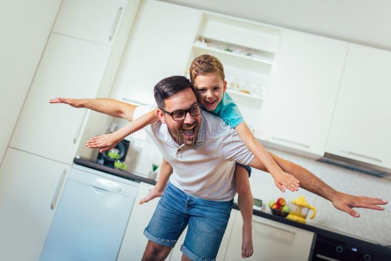 Удовлетворяемый усмехаясь человек перевозя по железной дороге его сына пока имеющ потеху в современной квартира-студии стоковое изображение rf