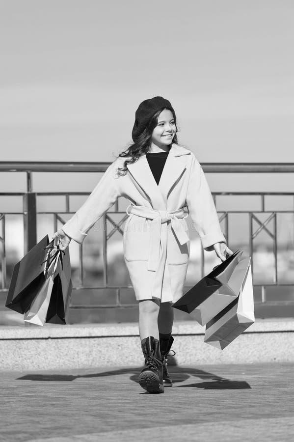 Удовлетворяя ходя по магазинам день Хозяйственные сумки пука владением ребенка стильные Пальто и берет дамы девушки милое маленьк стоковое изображение